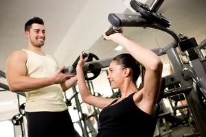 Fitness trainer helping woman